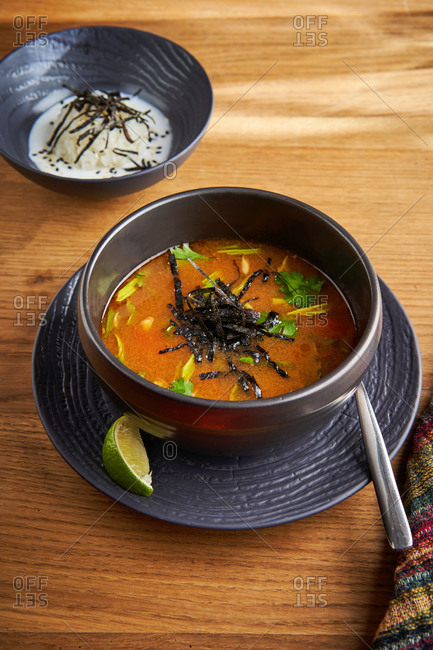 Asian hot and sour soup garnished with seaweed and served with a bowl of rice on wood background