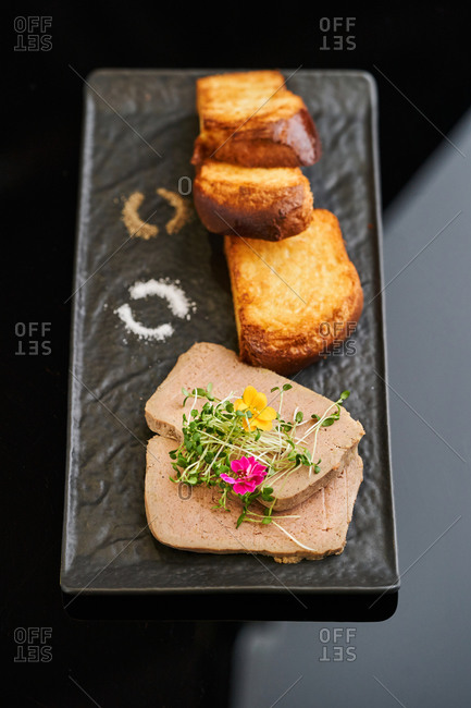 Creamy goose liver pate served with toasted brioche, edible flowers and microgreens on black serving dish