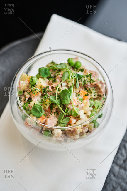 Traditional Polish vegetable salad with mayonnaise and ox tongue in a glass bowl