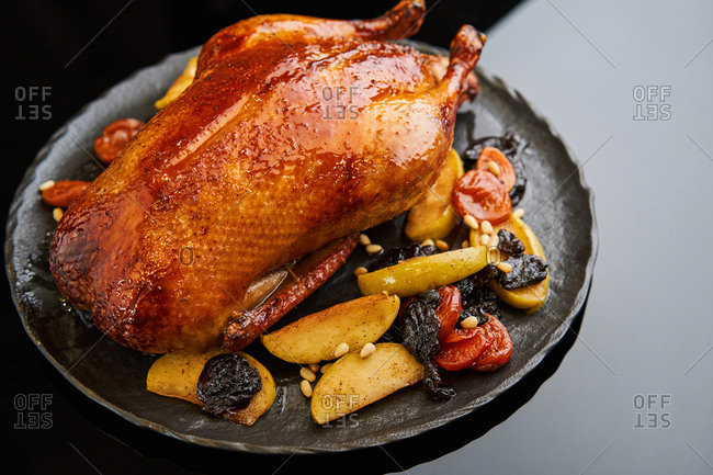 Festive dish of whole roasted duck with apples and fruit compote