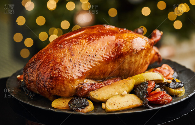 Roasted whole duck with apples, dried fruits and pine nuts served on black dish