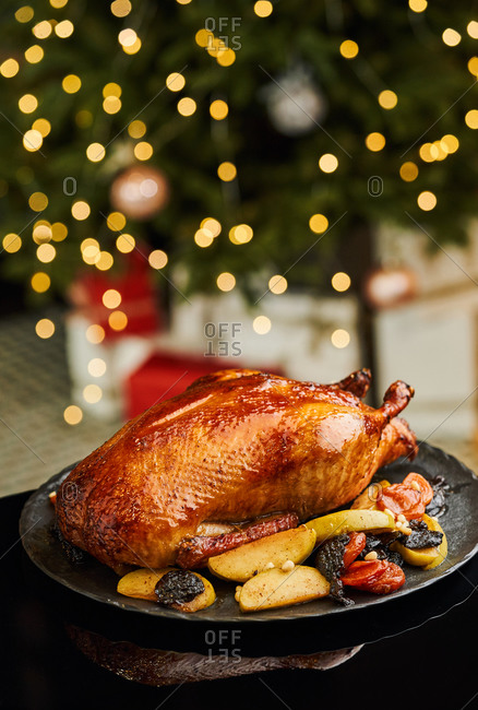 Roast duck with apples on glittering festive background