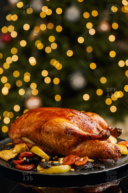 Holiday family dish of butter roasted duck served with apples and various dried fruits