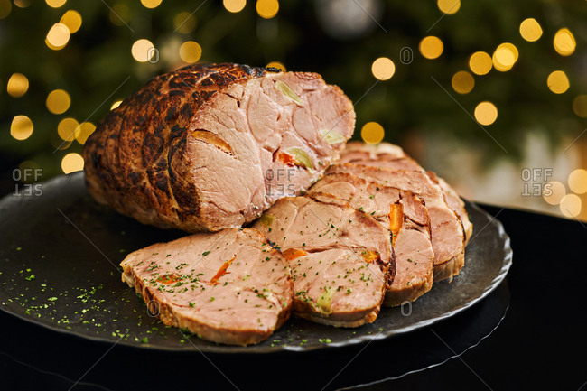 Baked pork loin stuffed with carrot and garlic served on black dish