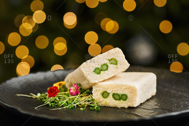 Cod Terrine with Asparagus served with edible flowers on glittering background