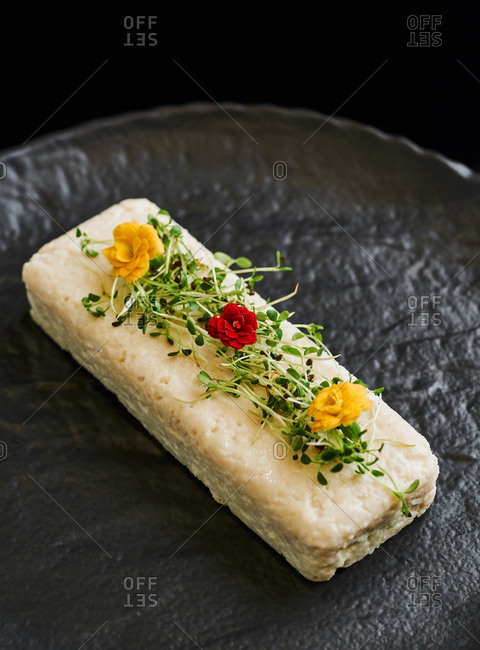 Elegant appetizer of white fish pate with edible flowers on black plate