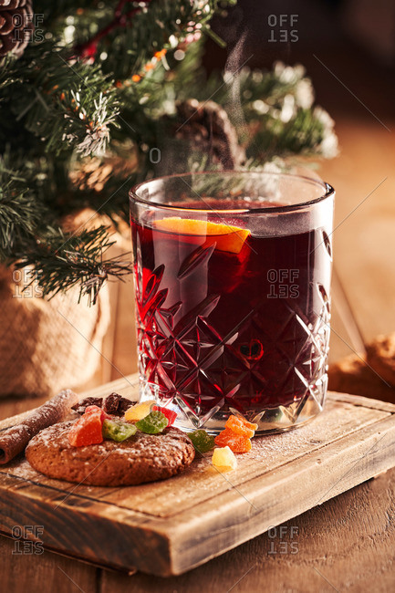 Mulled wine hot drink with citrus, apple and spices. Served with gingerbread cookie on wooden board.