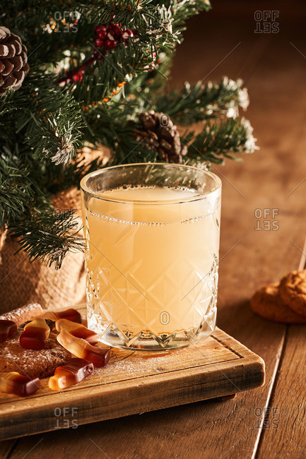 German mulled white wine hot drink with citrus and spices on wood background