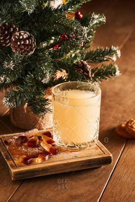 Hot mulled white wine cocktail served in a glass on wooden board