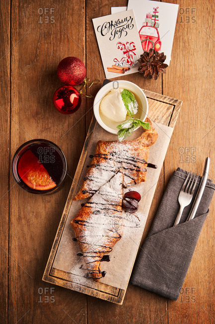 Apple strudel with icing sugar and vanilla ice cream served on wood background with Christmas decorations