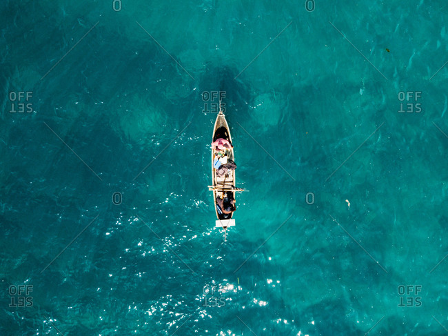 Aerial view of fisherman on canoe and turquoise water in Aceh, Indonesia.
