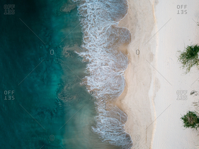 Aerial view of sandy beach with wave and grass in Lampuuk, Aceh, Indonesia.