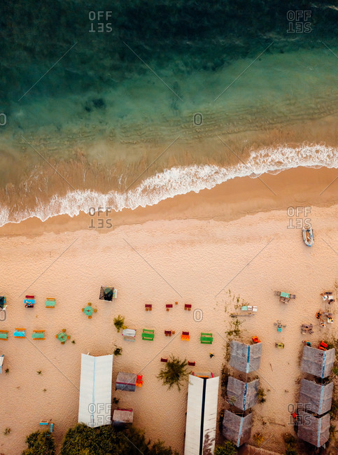 Aerial view of sandy beach with cafe and wave in Lhoknga, Aceh, Indonesia.