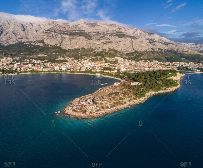 Aerial view of famous lighthouse and Adriatic sea coastline in the city of Makarska in Dalmatia, Croatia. Lighthouse is situated on the St. Peter peninsula. Biokovo mountain and Makarska city are also visible.