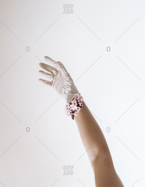 Latex glove covered hand with cherry blossom bracelet
