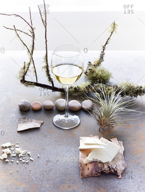 Glass of white wine surrounded by natural products and cheese