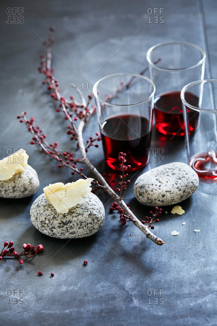 Glasses of pinot noir on gray surface with cheese