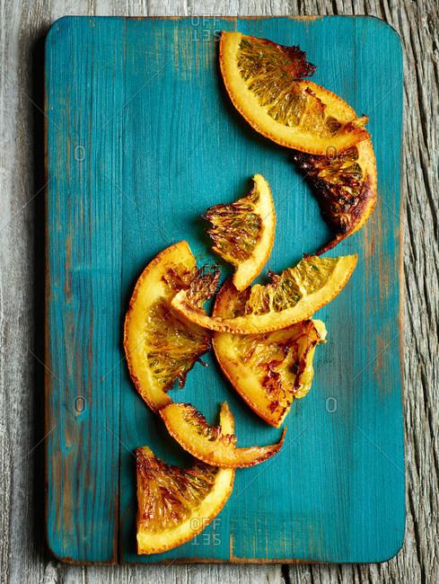 Roasted orange slices on blue wooden board