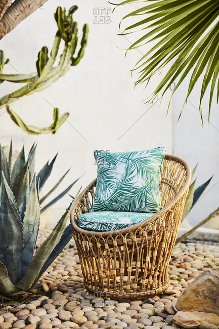 Wicker chair with cushions outdoor in stone garden