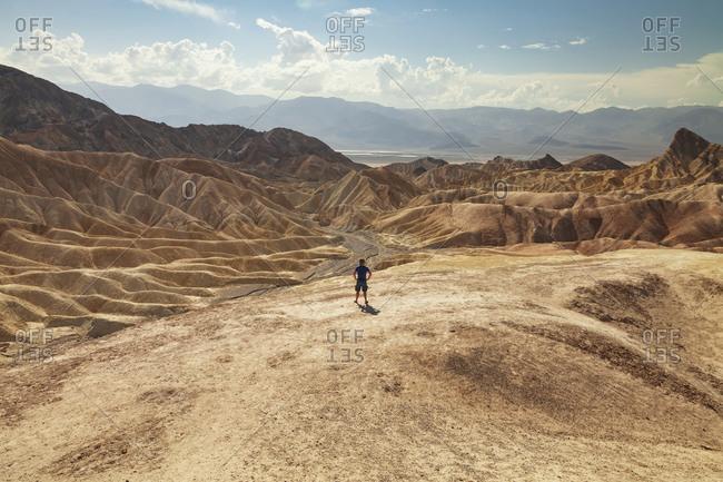Man overlooking desert hills under cloudy sky