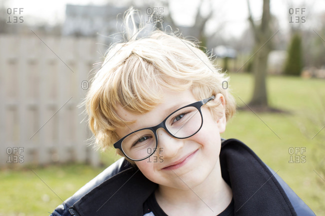 Portrait of cute blonde boy with glasses outside