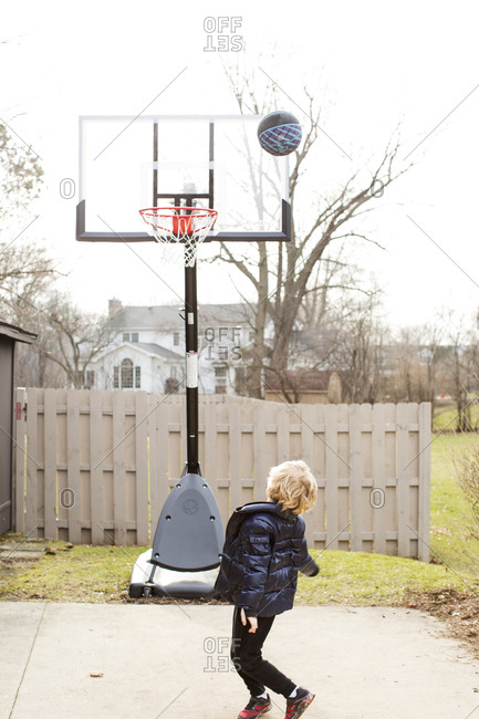 Blonde child plays basketball on his driveway