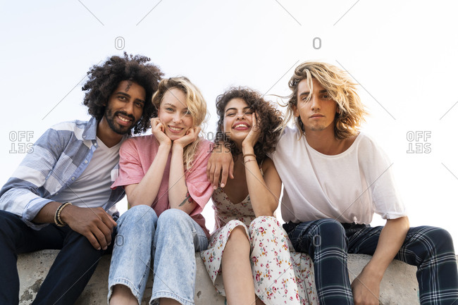Portrait of happy friends sitting on a wall outdoors