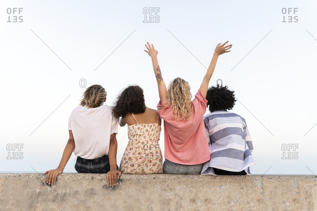 Rear view of happy friends sitting on a concrete wall outdoors
