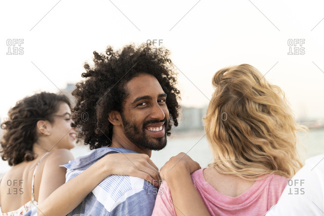 Portrait of happy friends embracing outdoors