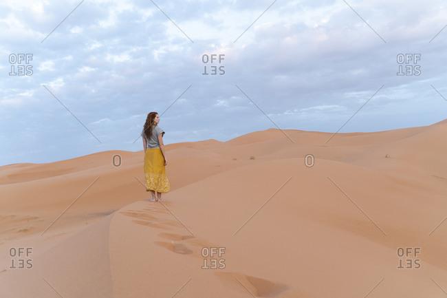 Young woman on sand dune in Sahara Desert- Merzouga- Morocco