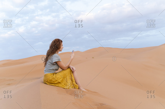 Young woman sitting in sand dune in Sahara Desert using cell phone- Merzouga- Morocco