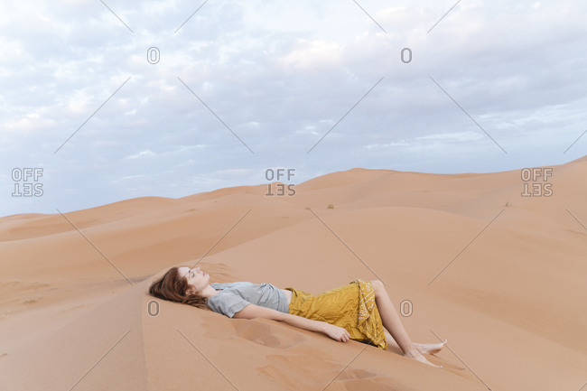 Young woman lying in sand dune in Sahara Desert- Merzouga- Morocco
