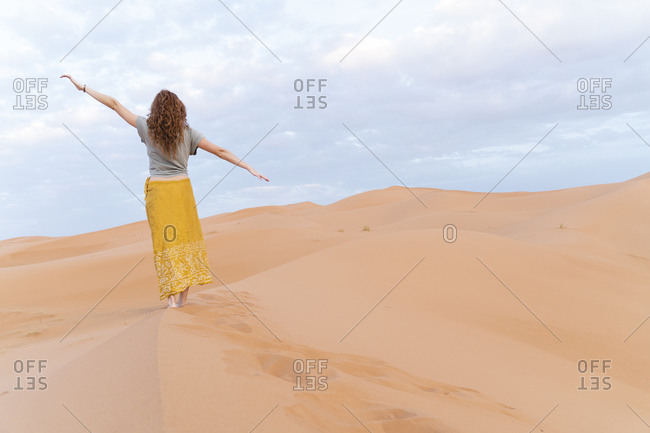 Young woman standing on sand dune in Sahara Desert with outstretched arms- Merzouga- Morocco