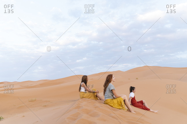 Three young women sitting in sand dune in Sahara Desert- Merzouga- Morocco