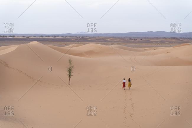 Two young women walking in Sahara Desert- Merzouga- Morocco