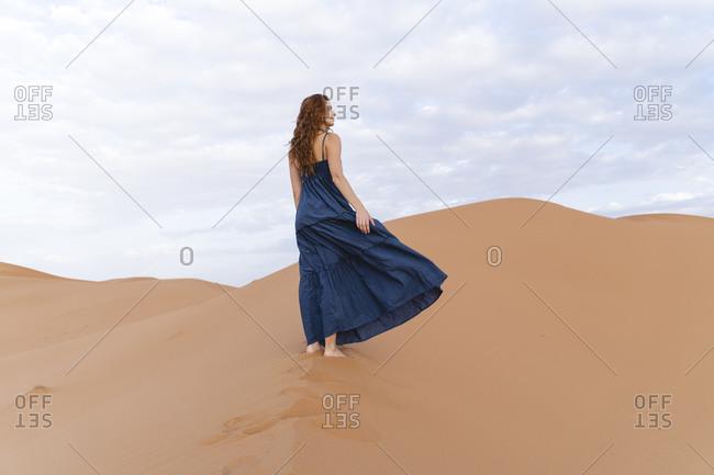 Young woman standing on sand dune in Sahara Desert- Merzouga- Morocco