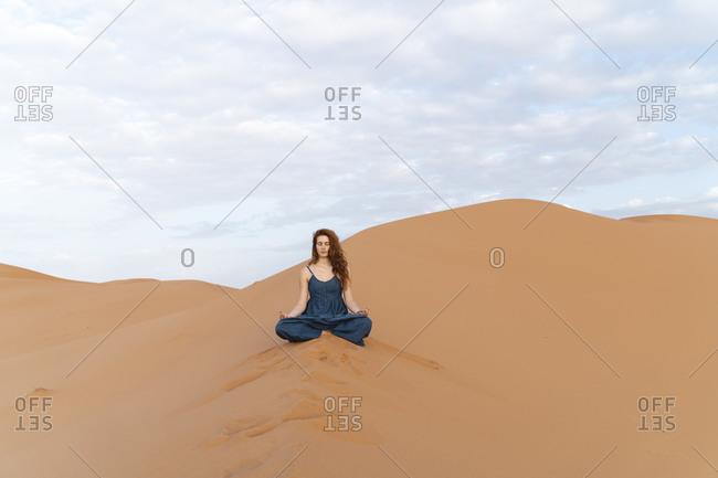 Young woman sitting in sand dune in Sahara Desert practicing yoga- Merzouga- Morocco
