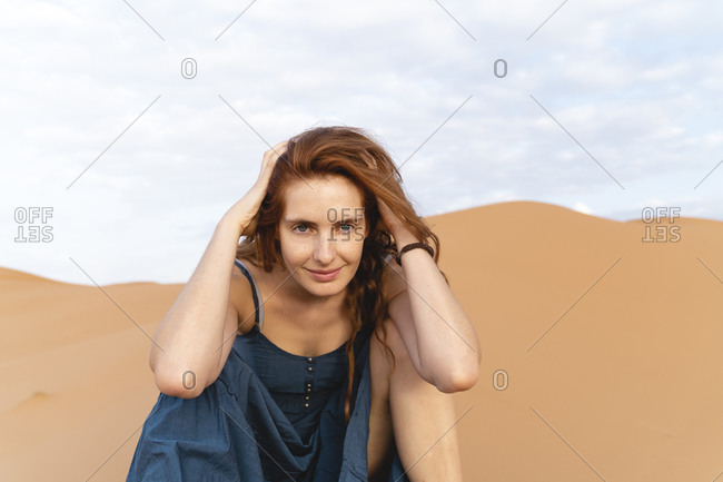 Portrait of smiling redheaded young woman in Sahara Desert- Merzouga- Morocco