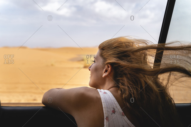 Young woman in car leaning out of window in Sahara Desert- Merzouga- Morocco