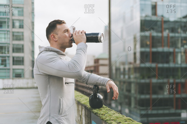 Man having a break from working out with a kettlebell in the city- Canada