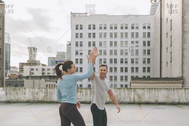 Man and woman high five during a workout in the city- Vancouver- Canada