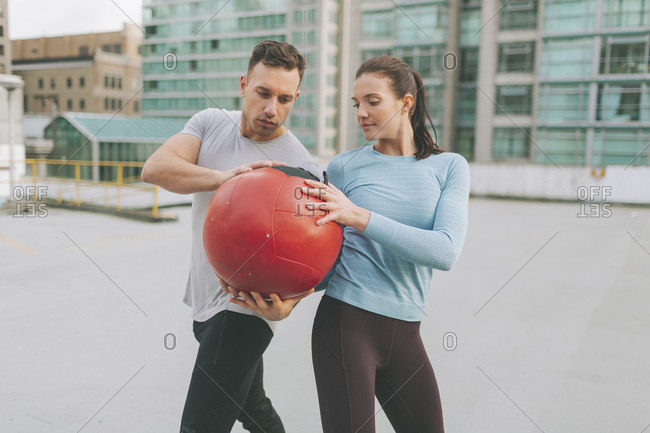 Man and woman exercising with a medicine ball in the city- Vancouver- Canada