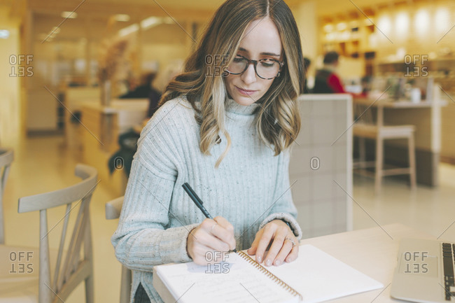 Blond woman sitting in a cafe and writing into notepad