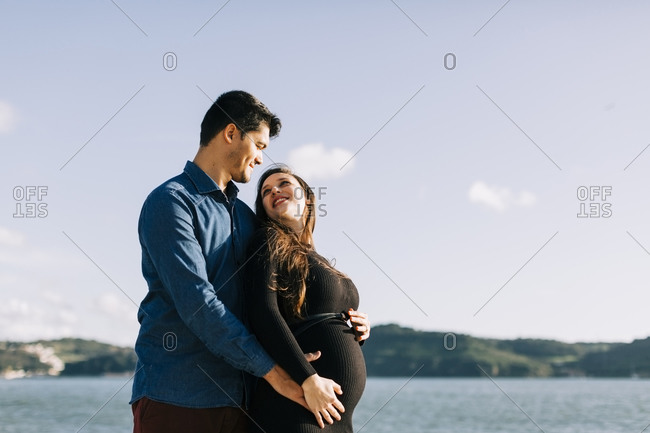 Affectionate expectant parents at the waterfront
