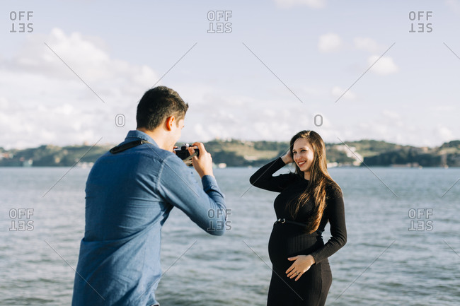 Young man photographing his pregnant girlfriend at the waterfront