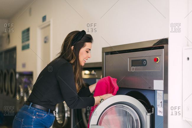 Young woman doing the laundry in a launderette