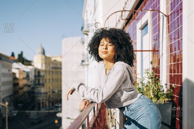 Portrait of young woman with curly hair standing on balcony enjoying the sunshine