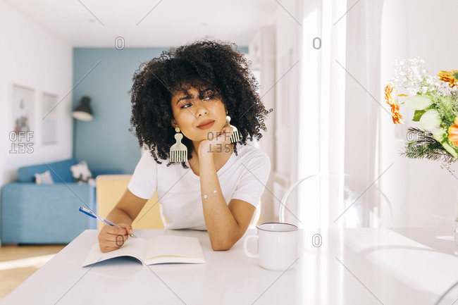 Portrait of young woman with curly hair sitting at a table with a notebook at home