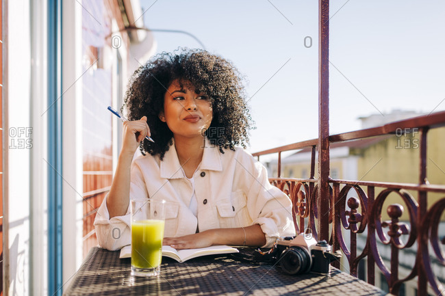 Smiling young woman with curly hair sitting at table on balcony with notebook- smoothie and camera
