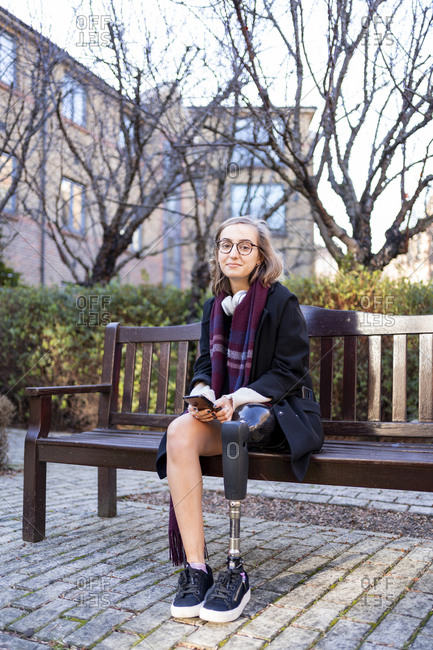Portrait of confident young woman with leg prosthesis sitting on a bench in the city